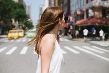 Young Woman Walking Across City Street