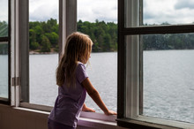 Girl Looking Out Of Boathouse Window