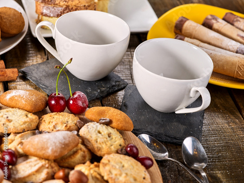 Oatmeal cookies and sand chocolate cake with cherry berry and crispy wafer rolls with cream on cutting board on wooden table in rustic style. Still life served with cups and dessert spoons.