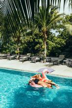 Couple Lying Floating On Flamingos