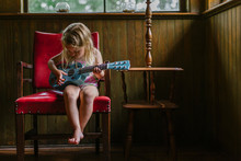 Family Lifestyle Image Of Young Girl Playing Guitar