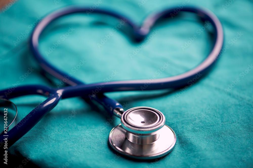 Fototapety, obrazy: A stethoscope shaping a heart on a medical uniform, closeup