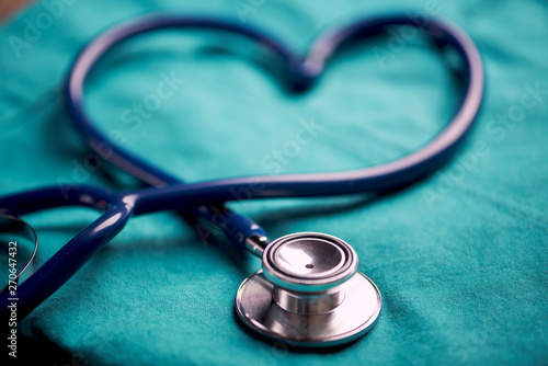 Fotomural  A stethoscope shaping a heart on a medical uniform, closeup
