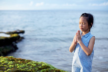 Cute Beautiful Asian Little Girl Praying With Hands Closed At The Seaside