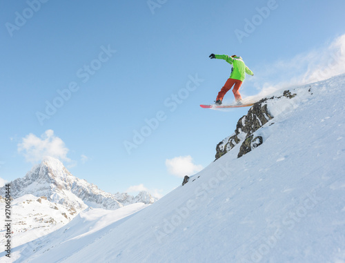 Snowboarder making a drop