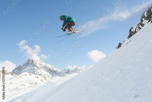 Male skier jumping from cliffs