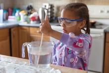 Portrait Of A Young Female Child Mixing A Solution For A Science Experiment