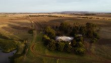 Aerial View Of A Rural Farms Homestead Sits Amongst Tall Trees And Vast Open Countryside Land On Sunset