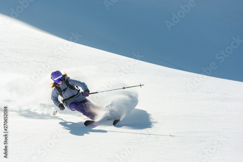 Freeride skier skiing downhill