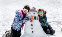 Two Little Sisters With A Snowman