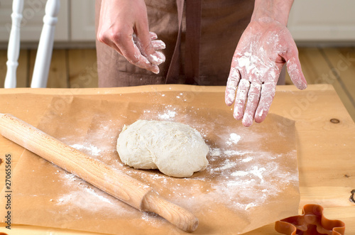 Deurstickers Bakkerij female hands rolling out dough with a rolling pin
