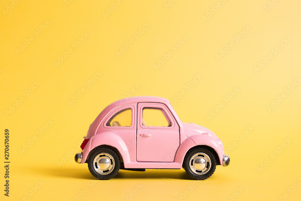 Fototapety, obrazy: Omsk, Russia - May 26, 2019: Pink retro toy car on yellow background. Valentines day. 8 March. Summer travel concept. Taxi.