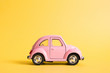 canvas print picture - Omsk, Russia - May 26, 2019: Pink retro toy car on yellow background. Valentines day. 8 March. Summer travel concept. Taxi.