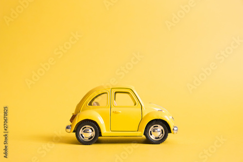 Poster Vintage voitures Omsk, Russia - May 26, 2019: Yellow retro toy car on yellow background. Valentines day. Womens Day. Summer travel concept. Taxi