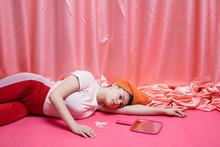 Thoughtful Young Woman Lying On Floor