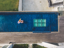 Young Woman Floating In Huge Swimming Pool On Inflatable Donut S