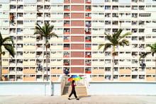Woman Walking Under The Sun With A Rainbow Umbrella