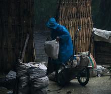 Man Unloading Sack Under Rain