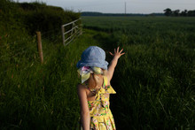 A Little Girl Stretches Her Hand In Front Of Her As She Strides Through A Field Of Green Crops.