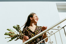 Portrait Of Smiling Young Woman Holding Flowers On Staircase