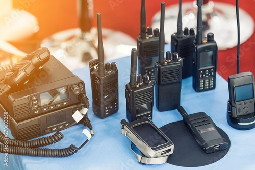 Obraz Many portable radio transceivers on table at technology exhibition. Different walkie-talkie radio set. Communication devices choice for military and civil use - fototapety do salonu