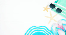 Beach Accessories On A White Wood Background. Summer Vacation Concept Banner With Copy Space. Sunglasses, Sea Shells, Towel, Flip Flops, And Blue Striped Hat.