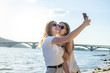 young beautiful girls on the beach, using a smartphone, they take a selfie on the background of the sea
