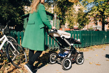Mother Pushing Daughter In Carriage While Walking By Fence In City