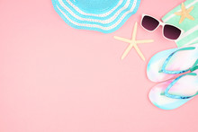 Beach Accessories On A Pink Background. Summer Vacation Concept Corner Border With Copy Space. Sunglasses, Sea Shells, Towel, Flip Flops And Blue Striped Hat.