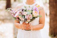 The Bride Holds A Wedding Bouquet. Delicate Bouquet With Yellow Roses And Eucalyptus.