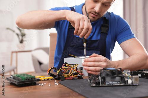 Fotografía  Male technician repairing power supply unit at table indoors