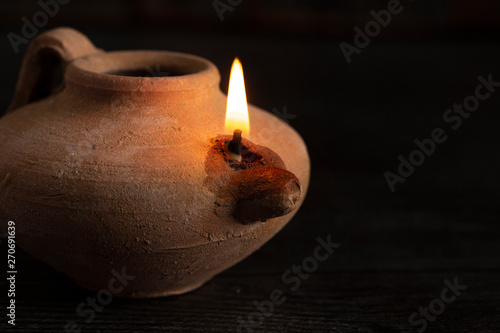 Fotografiet  A Lit Handmade Oil Lamp from the Middle East on a Dark Table