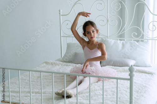 Fototapeta Cute pink dresses little girl 9 year dancing ballet with white bed in bedroom at home, Ballerina young girl practicing ballet dance at room. Kid ballet and performance art for modern concept. obraz
