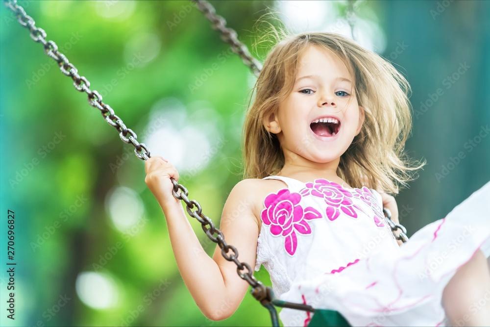 Fototapeta Little child blond girl having fun on a swing
