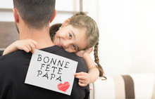 Little Girl Hugging Her Father And Showing The Message Of Congratulation.with French Text