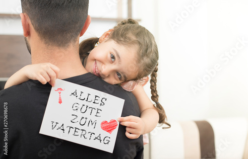 Foto auf Leinwand Texturen german lettering, fathers day happy birthday message.little girl hugging her father and showing the message of congratulation