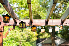 Closeup Of Patio Outdoor Spring Garden In Backyard Of Home With Lantern Lamps Lights Hanging From Pergola Canopy Wooden Gazebo And Plants