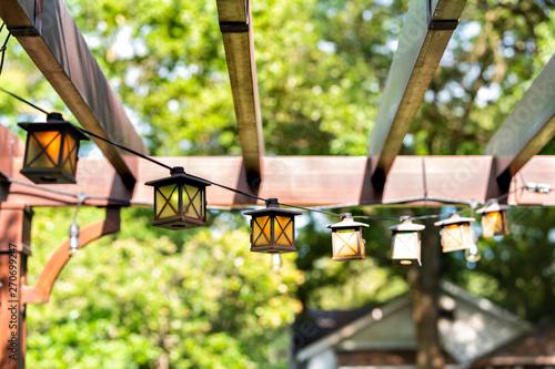 Closeup of patio outdoor spring garden in backyard of home with lantern lamps li Fototapeta
