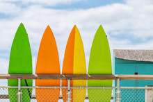 Stack Row Of Multicolored Colorful Stand Up Surfing Boards On Railing Fence With Green Orange And Yellow Color Against Blue Sky Lifeguard Tower Or Rental Shop