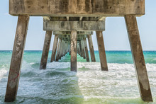 Under Underneath Okaloosa Fishing Pier In Fort Walton Beach, Florida With Pillars, Green Shallow Waves In Panhandle, Gulf Of Mexico On Summer Sunny Day