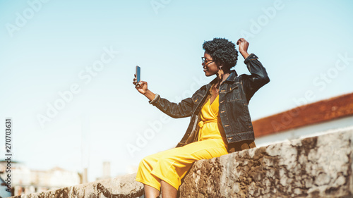 Stampa su Tela  Dazzling black girl with curly Afro hair is taking a selfie on the smartphone ou