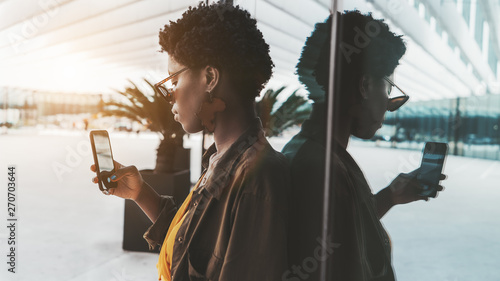 Fotografie, Tablou  Side view of an elegant African female hipster taking a photo using her smartpho