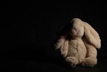 Soft Toy  Rabbit On A Dirty Dark Background In The Beam Of Hard Light With Shadow. Lost Childhood Concept