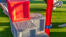 Panorama Frame Steps Going Up The Slide Against Rich Green Lawn At A Playground On A Sunny Day