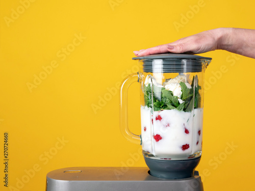 Blender on a yellow background. Strawberries, milk, mint, ice cream. Preparation of milky fruit drinks, smoothies, shake, cocktail. - 270724660
