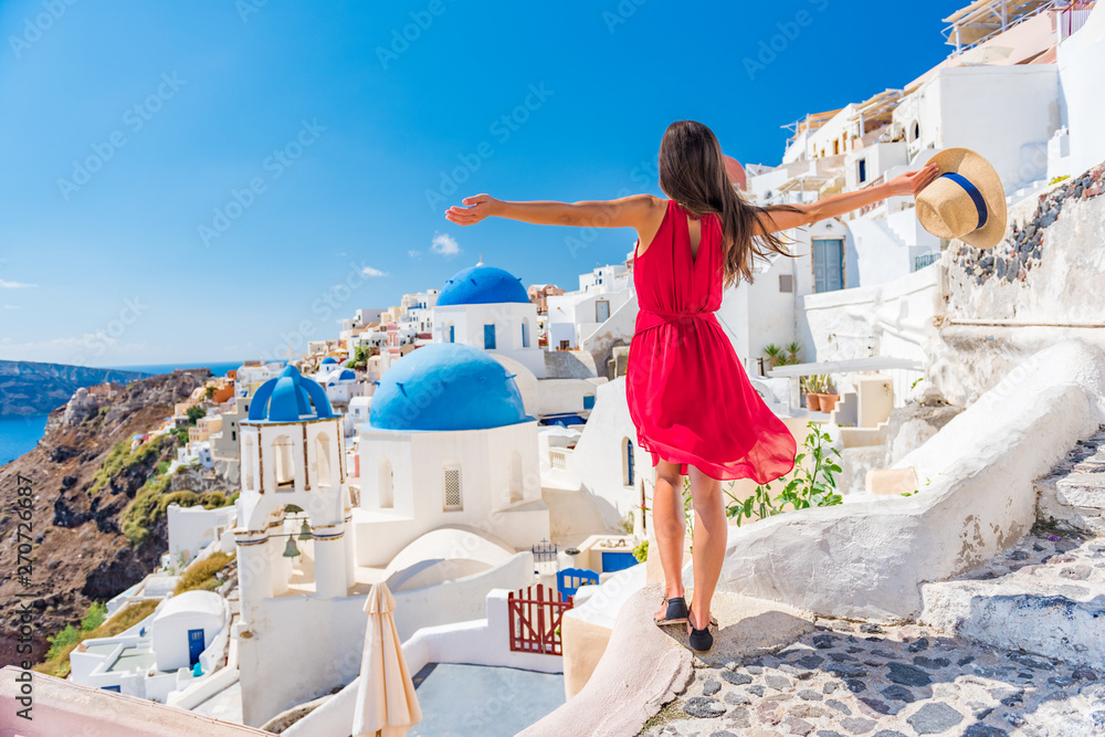 Fototapeta Europe travel vacation fun summer woman dancing in freedom with arms up happy in Oia, Santorini, Greece island. Carefree girl tourist in European destination wearing red fashion dress.