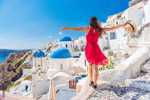 Fototapeta Europe travel vacation fun summer woman dancing in freedom with arms up happy in Oia, Santorini, Greece island. Carefree girl tourist in European destination wearing red fashion dress. obraz