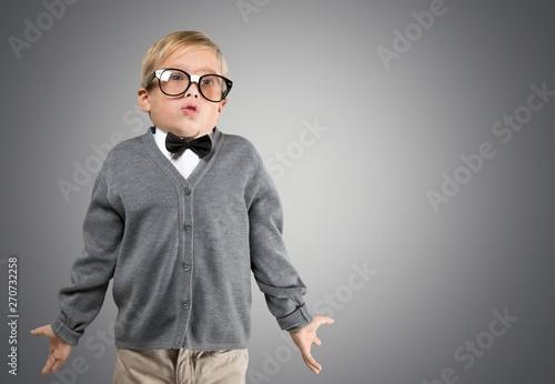 Stampa su Tela  Cute little schoolgirl on blackboard background