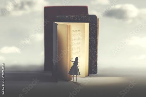 Fotografie, Obraz  curious woman looks into a mysterious illuminated book