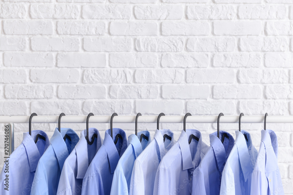 Fototapety, obrazy: Rack with clothes after dry-cleaning near white brick wall
